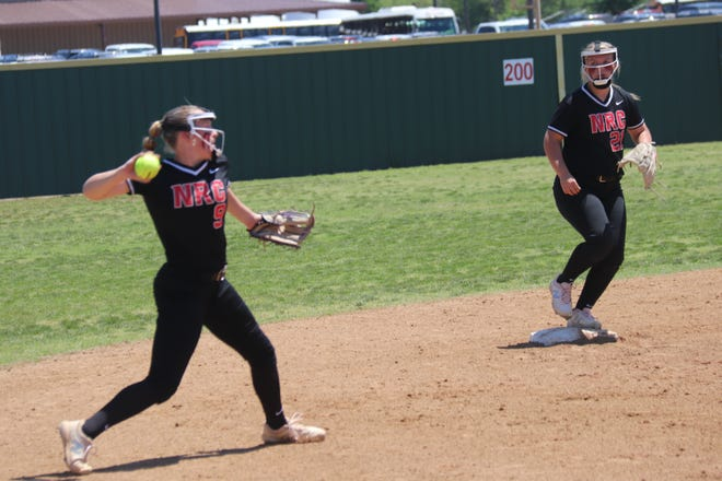 North Rock Creek shortstop Haley Hacker (left) fires the ball to first base for the out as teammate and second baseman Raynee Bass looks on.