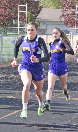 Bronson's Jenna Salek takes the baton from her teammate Grace Welch for the anchor leg of the 880 yard relay Wednesday.