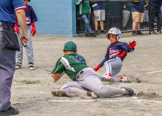Max Mutnansky of DeBross Oil is safe at home as he just beats the tag of K & B pitcher Jean Rodriquez. K & B would go on to defeat DeBross 11-2.