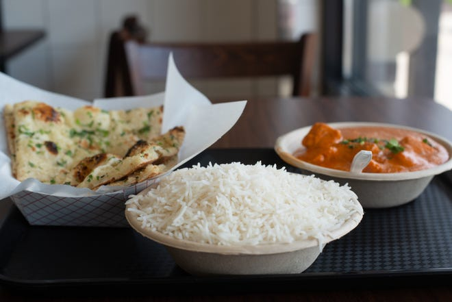 The chicken tikka masala from Pal Indian Cuisine is served with a side of rice. Order garlic naan bread to complete the meal.