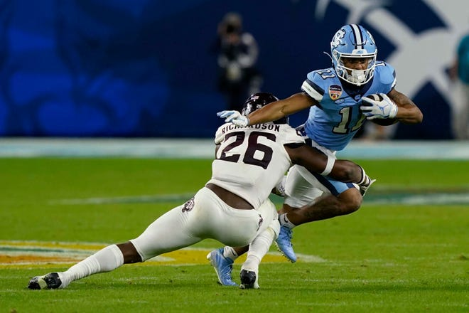 North Carolina's Josh Downs, right, tries to elude the tackle of Texas A&M's Demani Richardson during the Orange Bowl in January.