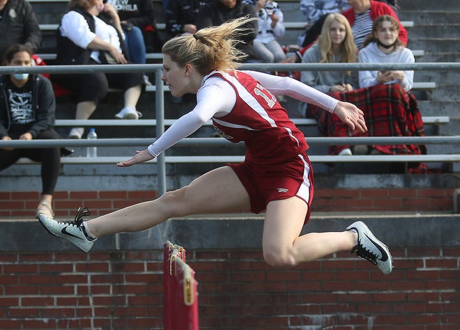 Dover's Meghan McCrate wins the 100 meter hurdles at the Dover-New Philadelphia dual track meet Thursday.