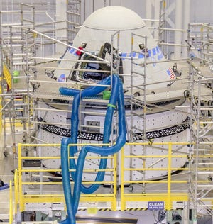 The Starliner spacecraft that will fly Boeing's Orbital Flight Test-2 mission to the International Space Station is seen inside the Starliner production factory at Kennedy Space Center in Florida on April 28, 2021.