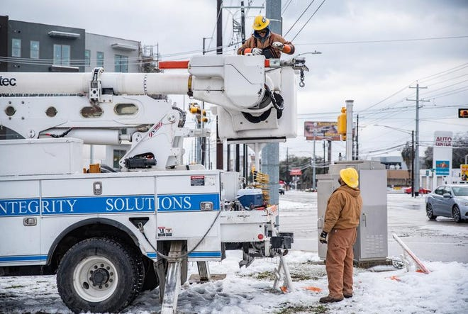 Electrical workers repair a power line in Austin on Feb. 18, 2021. Some of the state's electricity providers are financially underwater in the aftermath of the February power outages.