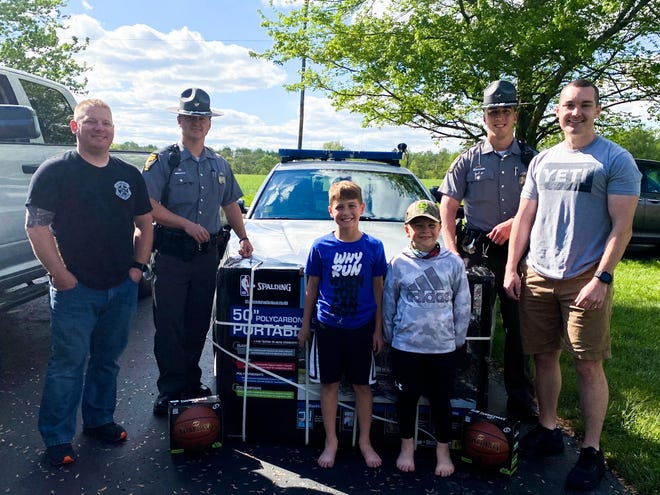 A Warren County sheriff deputy and some  Ohio State Highway Patrol troopers pitched in to buy a 9-year-old Warren County boy and his 6-year-old brother a new basketball hoop after a wreck in the boys' front yard destroyed their hoop. From left are Deputy Sean Mason, Trooper Adam Pollitt, Joel Steinmetz, Jacob Steinmetz, Trooper Benjamin Kirby and Trooper Patrick Wright.