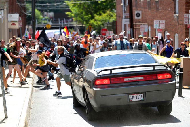 In this Aug. 12, 2017 file photo, a vehicle drives into a group of protesters demonstrating against a white nationalist rally in Charlottesville, Va.  A federal judge on Wednesday, May 5, 2021,  has ordered a right-wing think tank led by white nationalist Richard Spencer to pay $2.4 million to an Ohio man severely injured during a white supremacist and neo-Nazi rally two years ago in Virginia organized by Spencer.  Bill Burke says he was struck by a car driven by James Alex Fields Jr. , in a crash that killed counterprotester Heather Heyer, during the August 2017 rally in Charlottesville.