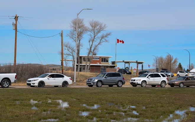 In this Wednesday, April 28, 2021, photo, cars line up at the Piegan-Carway border crossing between Montana and Canada, near Babb, Mont. The Blackfeet tribe gave out surplus vaccines to its First Nations relatives and others from across the border. (AP Photo/Iris Samuels)