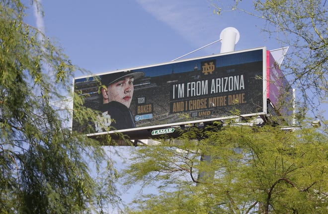 May 6, 2021; Tempe, Arizona, USA; Tosh Baker, former Pinnacle offensive lineman, who is now playing at Notre Dame, headlines a digital billboard at Tempe Marketplace. Patrick Breen-Arizona Republic