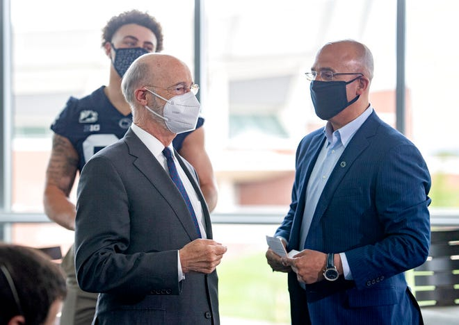 Gov. Tom Wolf talks with Penn State football coach James Franklin after he spoke about the importance of Pennsylvanians getting the coronavirus vaccine during a visit to Penn State's Pegula Ice Arena, Wednesday, May 5, 2021, in State College, Pa. (Abby Drey/Centre Daily Times via AP)