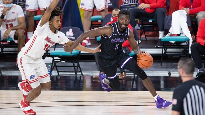 Northeastern High graduate Kobi Nwandu, right, dribbles past a defender while playing for Niagara University. Nwandu recently announced he will turn pro to pursue a basketball career.