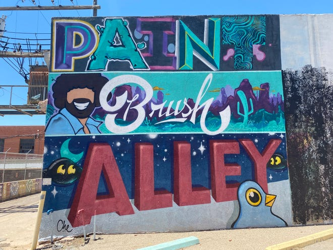 A colorful sign painted by artist Che Bates greets public art lovers at San Angelo's Paintbrush Alley in the parking lot next to 19 W. Twohig. May 6, 2021.