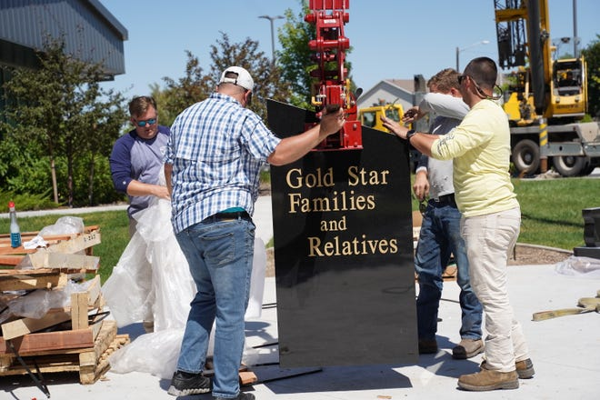 Workers install part of the Gold Star Families Memorial Monument in Ogden. St. George is planning to install its own memorial monument downtown at the Town Square park.