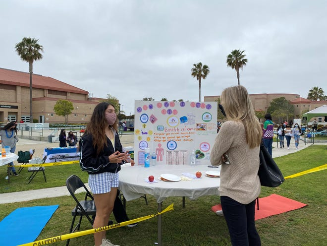 """Pacifica High student Emily Tejeda presents her project about exercise at the school health science academy's """"Boardwalk to Better Health"""" fair Thursday, May 6, 2021."""