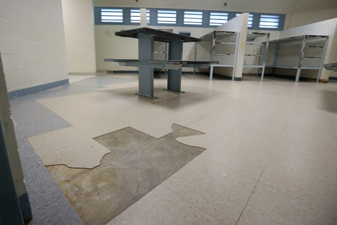 Damaged floor tiling is seen in a block cell on Tuesday, Feb. 2, 2021, at the Wood County Jail in Wisconsin Rapids, Wis.