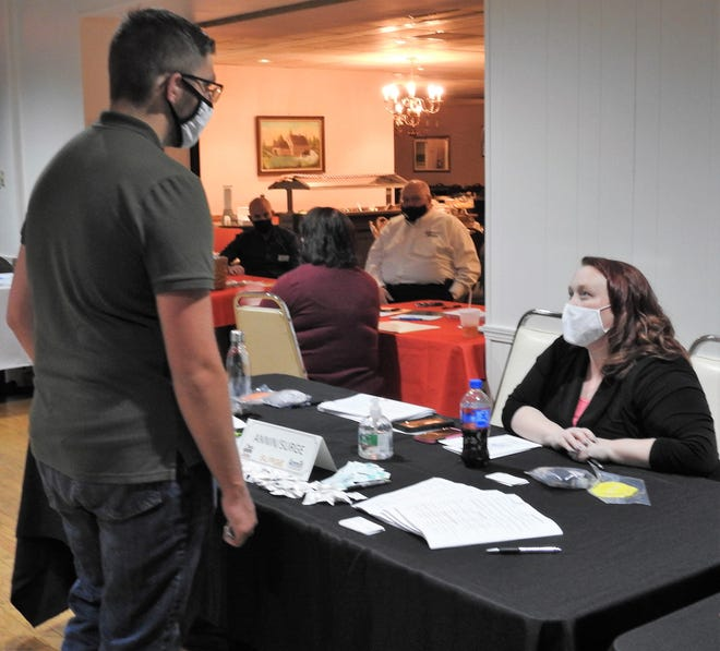 Melanie Hatcher, Workforce manager with Surge, talks to an employee candidate about Annin Flagmakers at a job fair Thursday at the Coshocton Elks Lodge through Ohio Means Jobs.