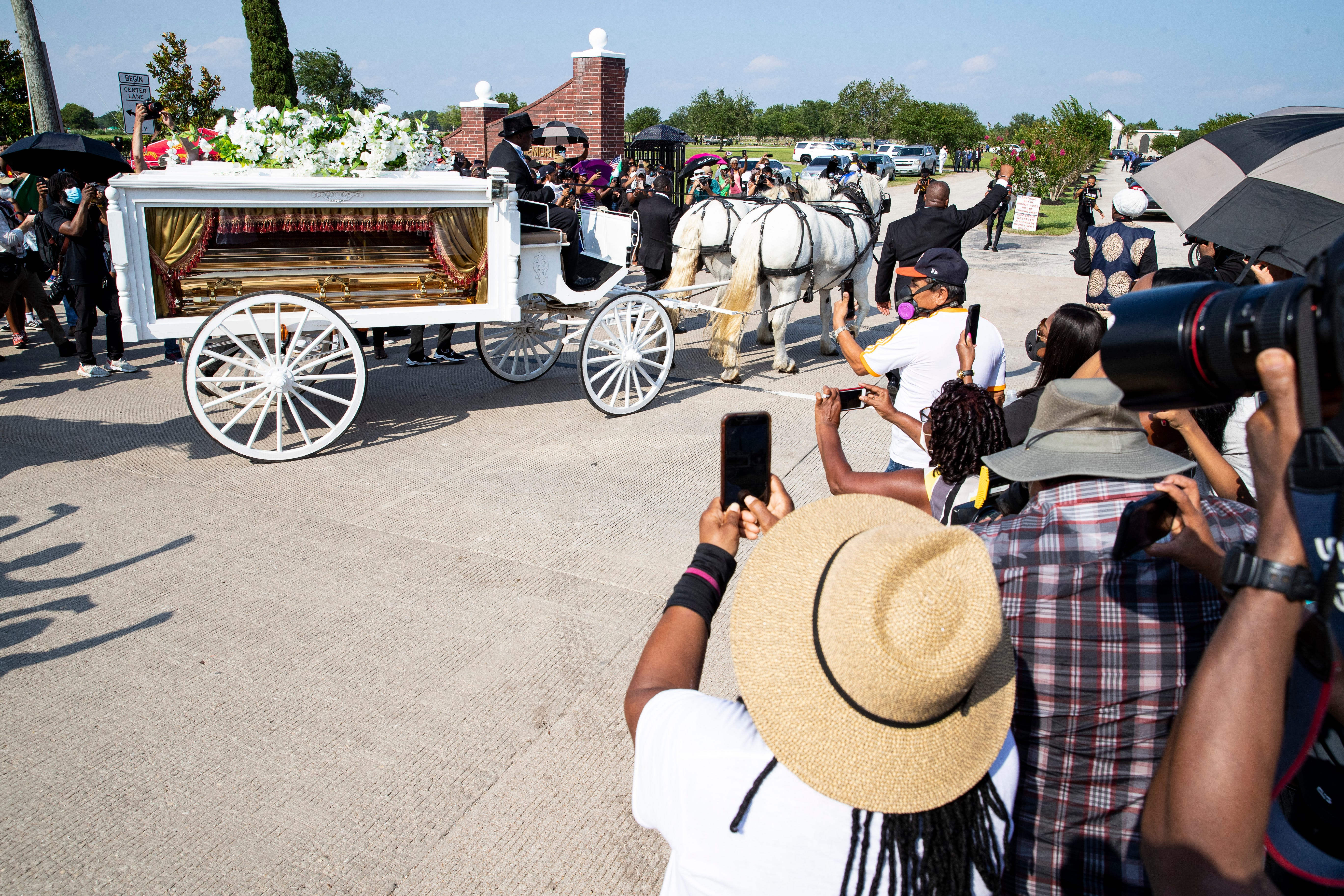 A horse drawn carriage carrying the casket of George Floyd arrives at Houston Memorial Gardens in Pearland, Texas on Tuesday, June 9, 2020.