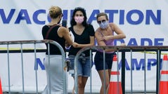 Women pose for a photo before getting their COVID-19 vaccines in Miami.