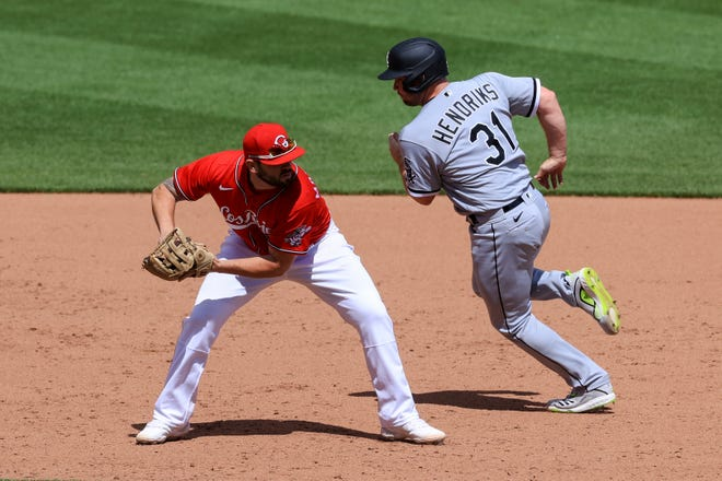Reds third baseman Mike Moustakas fields the ball as Liam Hendriks of the White Sox tries to avoid him in the 10th inning of Cincinnati's 1-0 win.