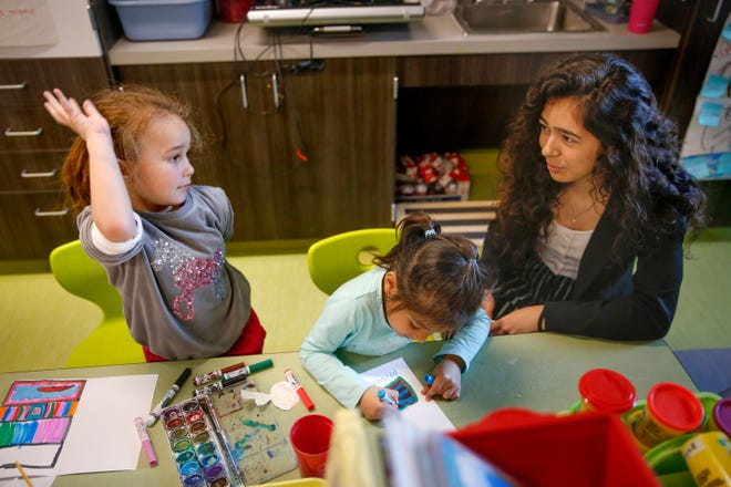 Jacquelin Arrieta, a student at Akins High School, is shown last year helping Presley Georg, then 5, left, and Priscila Alfaro, then 4, at a pre-K program at Menchaca Elementary. [JAMES GREGG/AMERICAN-STATESMAN]