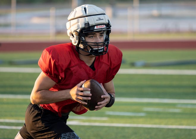 """Johnson quarterback Jesse Medina, who accounted for almost 2,000 yards of offense a year ago, goes through drills at a practice Thursday at Johnson High School in Buda. After his team missed spring practice last season because of the coronavirus pandemic, Medina says """"now, we just want to do what we know we can do and prove everyone wrong."""""""