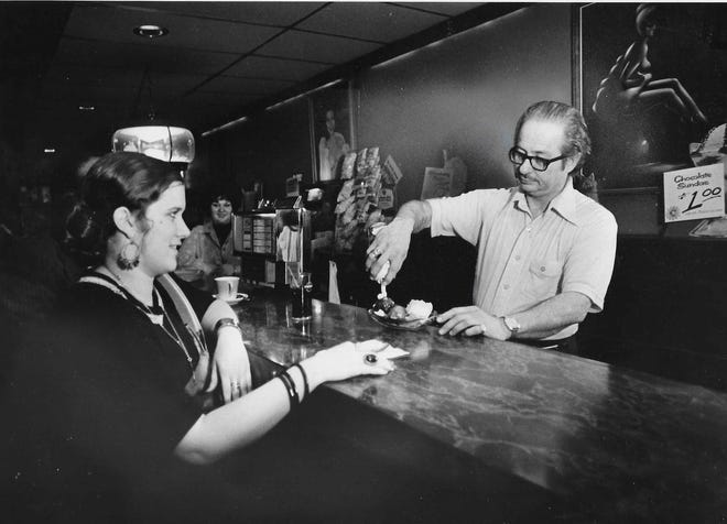Chat Noir proprietor Abe Katz makes a banana split for customer Cindy Dike on May 3, 1976. After his liquor license was suspended, Katz converted his downtown Akron bar into an ice cream parlor.