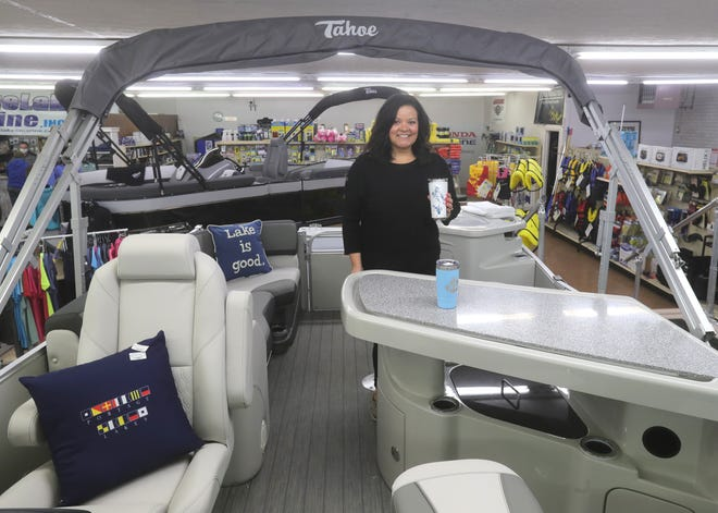 Portage Lakes Marine manager JoAnne Tyrrell stands in a new Tahoe Tritoon complete with a lighted bar Friday  in Coventry Township.