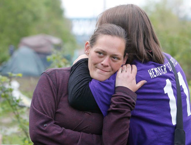 Becky Reeder, right, hugs Krystal at a homeless encampment Thursday in Akron. Both of the women are homeless and live in tents.