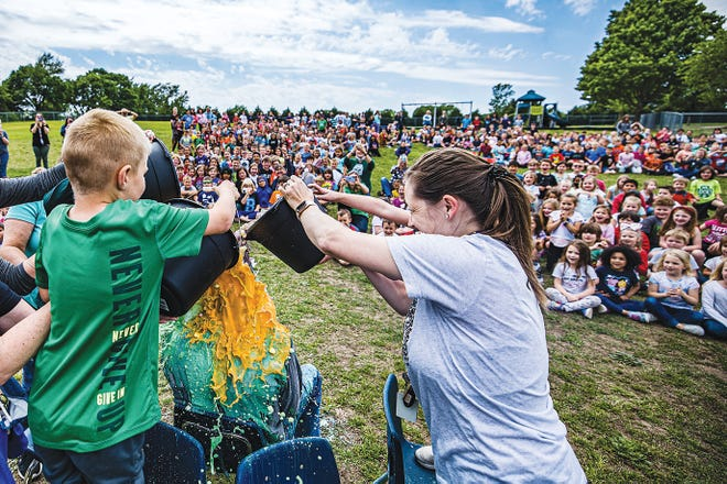 Wayside Elementary School students look on as Principal Ken Copeland gets slimed for the second time. The students earned the slime bath for Copeland after exceeding their goal of $30,000 during their annual walk-a-thon.