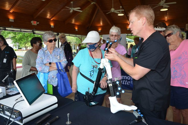 Sun City residents observe a robotic knee replacement demonstration at the Sun City Health Fair.