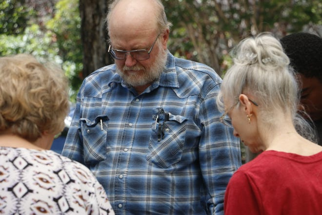 Waymon Childress of Life Point Baptist Church in Early prays with other community members Thursday at the Margaret and Stuart Coleman Plaza in Brownwood.