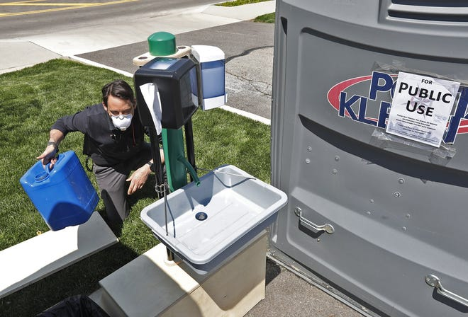 Steve Sauer of Bigger Tuna, a design firm, shows off the water receptacle for the portable hand washing station located at Cleveland Avenue and East Broad Street last May. The 14 sinks were installed around Columbus for people without access to a restroom.