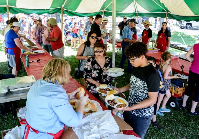 Area residents make their way through the food serving lines in a tent during a past Beef Empire Days Chuckwagons at the Zoo Community Feed on the west lawn of Lee Richardson Zoo. Beef Empire Days will be returning this year with events after a year off from the COVID-19 pandemic.