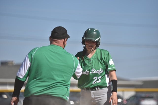"""Geneseo's Maya Bieneman, No. 23, gets a """"high five"""" from Coach Tom Rusk after her triple."""