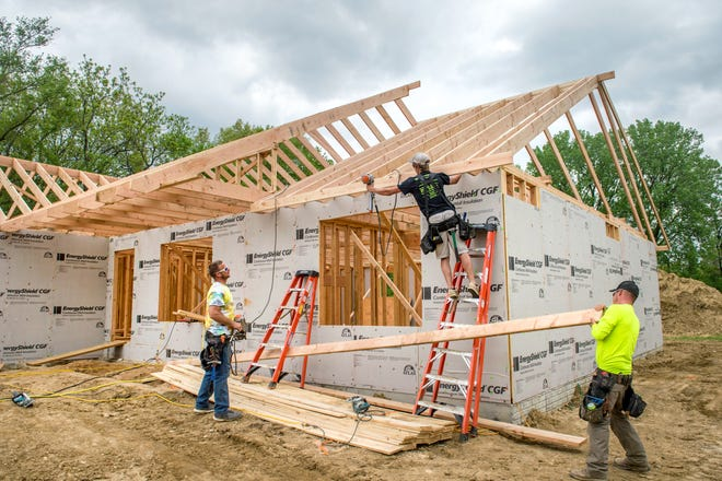 Contractors for P&W Builders work on a house on Greenview Drive in East Peoria.