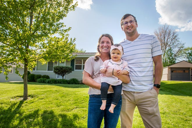 Luke and JaNae Hoerr pose with their 10-month-old daughter, Palmer, outside the young family's home in Peoria. The Hoerrs managed to successfully navigate the current seller's market to purchase their first home.