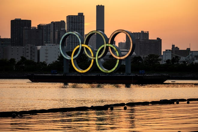 The Olympic rings are lit at the waterfront of Odaiba in Tokyo on April 20, 2021. (Philip Fong/AFP via Getty Images/TNS)