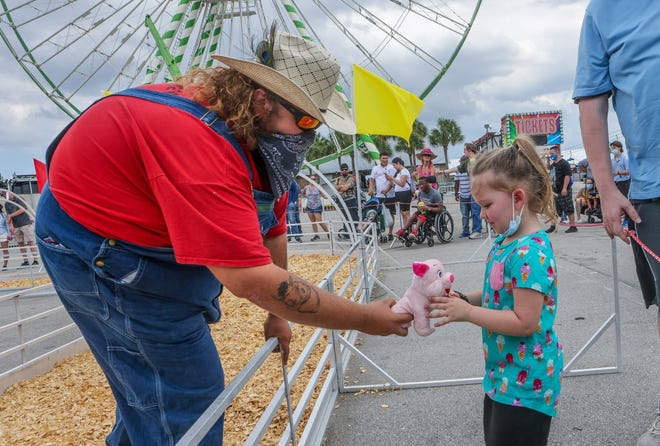 Colton Brooks, a.k.a. Pork Chop, awards 4-year-old Liliana Kueker of Texas a stuffed pig for guessing the winner of a pig race during the Show-Me Swine Racers event at the South Florida Fair on Friday.