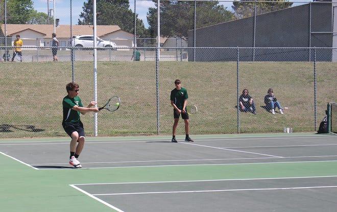 Pratt High School tennis player Rafe Donnenwerth serves as his doubles partner MIcah Tatro readies for the return.