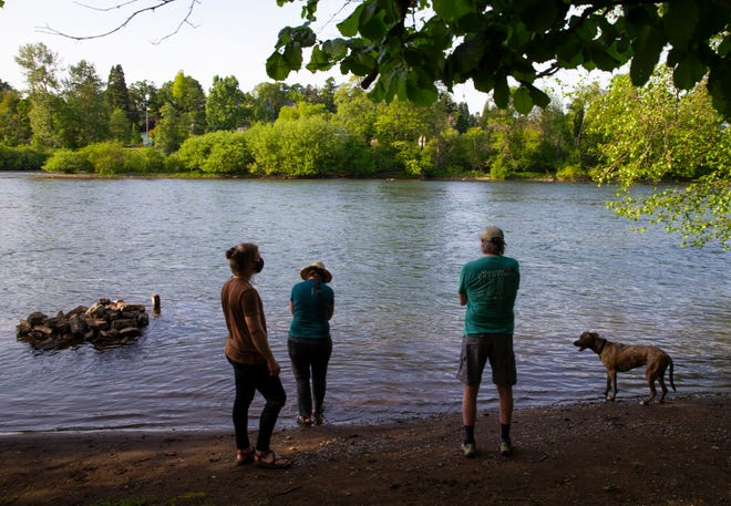 Neighbors Benjamin Cooper, left, Kellyn Gross, Joe Baker and dog Shayla visit the Willamette River in Glenwood on land where two developers have proposed to build large projects