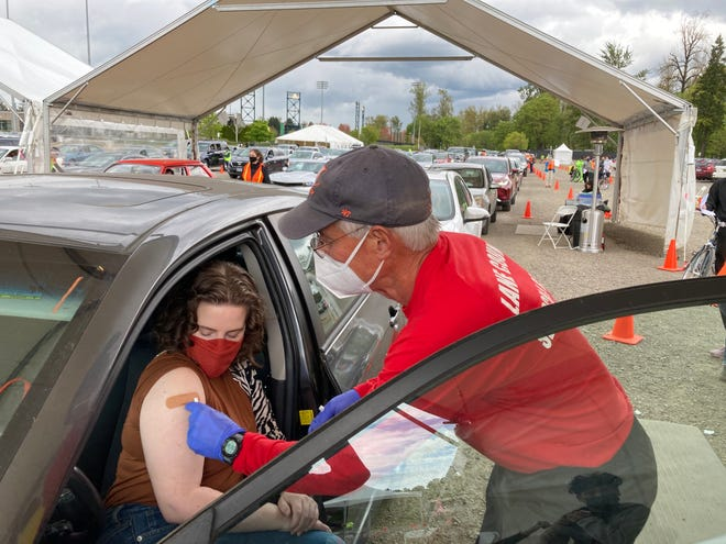 Registered nurse and Lane County Public Health volunteer Ed Willson places a bandage where he administered a COVID-19 vaccine while his patient, Gina Scalpone, looks on at a COVID-19 drive-thru in April.