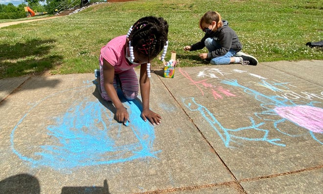 Hayben Cannon and Burlon James draw on the sidewalk at Township Three Elementary School.