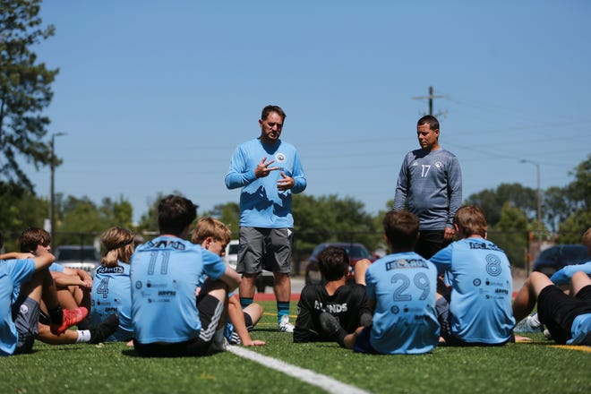 Islands High soccer coach Dante Casagrande talks with the team before the start of a recent practice.