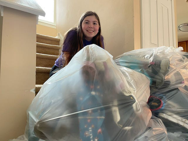 Olivia Bruno, a scout with Girl Scout Troop 547, shows off bags of shoes collected as part of the troop's fundraiser collecting new, used and gently worn shoes.