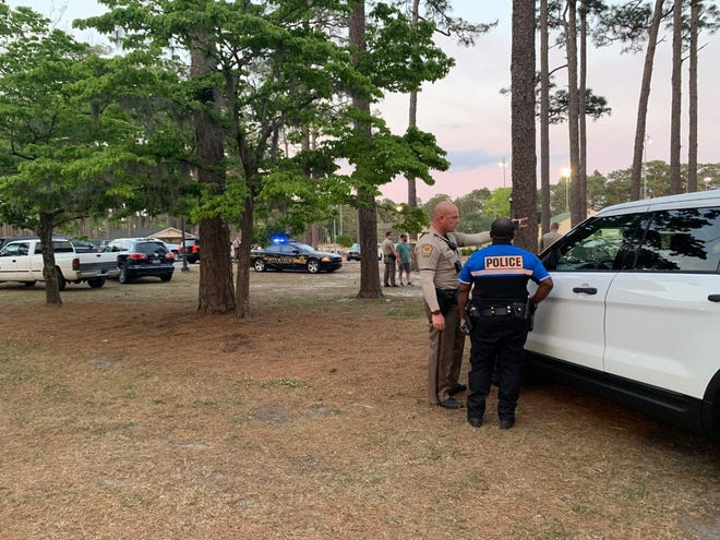 A Wilmington Police Department officer and a New Hanover County Sheriff's Office deputy communicate the details to each other at the scene of the Long Leaf Park shooting Wednesday night.