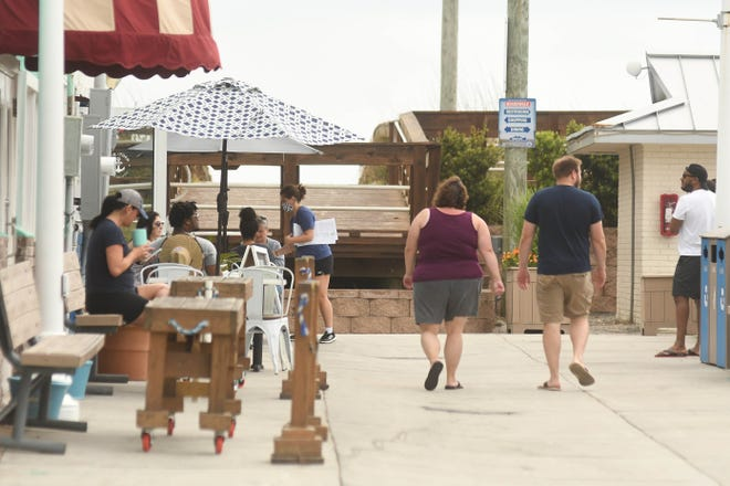 People walk around the Boardwalk in Carolina Beach, N.C., Monday May 3, 2021. Carolina Beach expects more tourists this summer than they usually see. The town has also seen a more than 30% increase in its population.