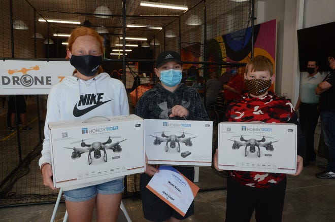Winning team members (from left) Harlee Blackwell, Wyatt Raines and Noah Howard pose with their new drones after taking first place in Thursday's drone competition at the Pitsco Idea Shop.