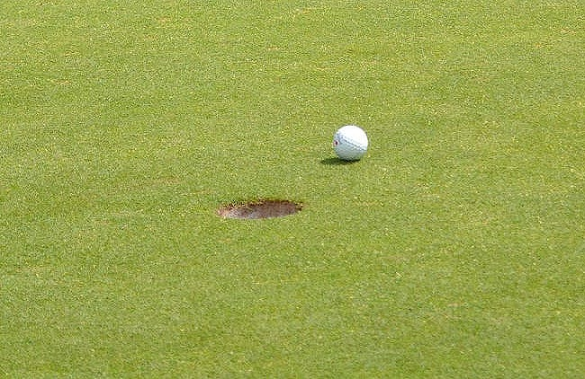 A golf ball rests near the cup.