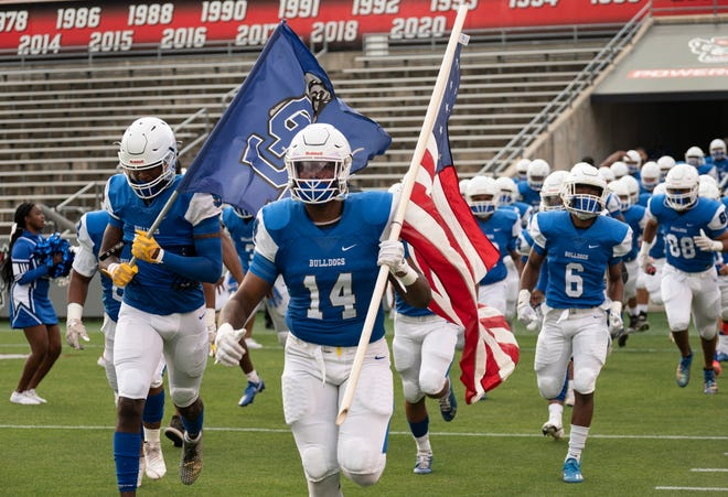St. Pauls senior Enrique Lopez-Ray (14) led the Bulldogs onto the field at Carter-Finley Stadium on Thursday. Despite a 42-14 loss in the NCHSAA 2-AA state championship, Lopez-Ray and head coach Mike Setzer reflected on a historic run for the program.