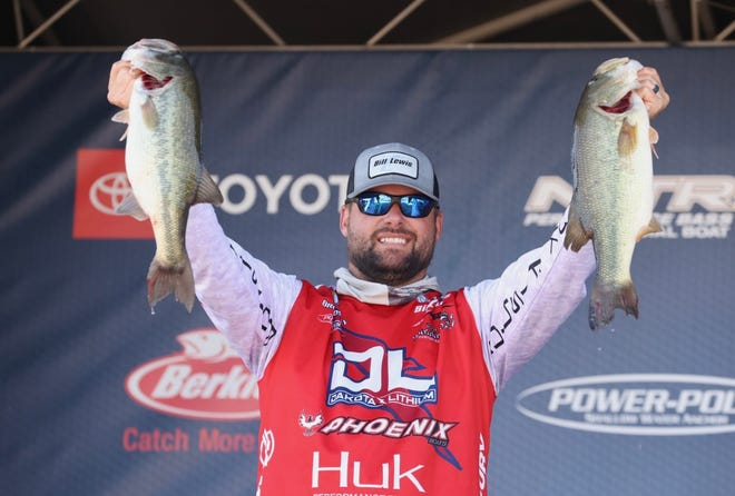 Brock Mosley holds up two of his catch after the first day of the Bassmaster Elite event on Neely Henry Lake in Gadsden on Friday. Mosley holds the lead going into the second day of the event.