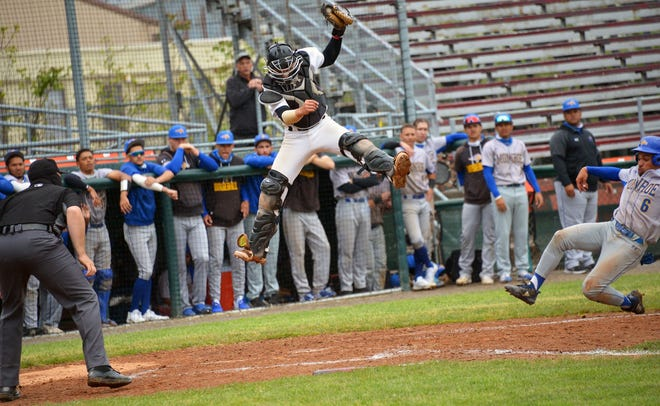 Hagerstown Community College catcher Brenden Moshos leaps to grab a high throw, but can't land in time as Monroe's Joan Sosa slides safely home for a run in the sixth inning of Friday's Region XX Tournament game at Municipal Stadium.